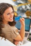 Frau mit Kreditkarte unter Verwendung des Laptops vor Weihnachtsbaum Lizenzfreies Stockfoto