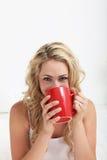 Frau mit lächelnden Augen Kaffee trinkend Stockbilder