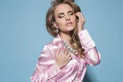 Frau mit langer gelockter eleganter Kleidung und Juwel des blonden Haares Stockfotos