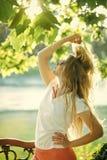 Frau mit langer Haltung des blonden Haares unter grünem Baum Stockfotos