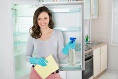 Frau mit Lappen und Sprühflasche nahe dem Kühlschrank lizenzfreies stockbild