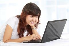 Frau mit Laptop auf Bett Lizenzfreie Stockfotografie