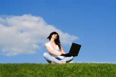 Frau mit Laptop auf dem grünen Gras Lizenzfreies Stockfoto