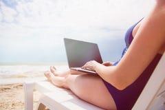 Frau mit Laptop auf dem Strand Stockfoto