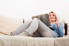 Frau mit Laptop auf der Couch, die okaygeste zeigt Stockfotos