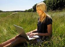 Frau mit Laptop auf einer Wiese Stockfotografie