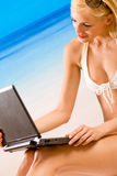 Frau mit Laptop auf Strand lizenzfreies stockfoto