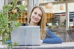Frau mit Laptop draußen Stockfotografie