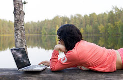 Frau mit Laptop nahe dem See Stockfotografie