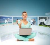Frau mit Laptop-PC und virtuellen Schirmen Stockbild
