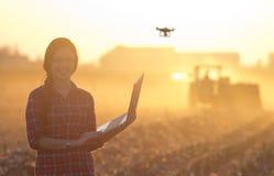 Frau mit Laptop und Drohne auf Feld Lizenzfreies Stockfoto