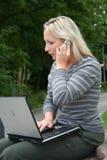 Frau mit Laptop und Handy Stockbild