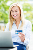 Frau mit Laptop und Kreditkarte Stockbild