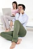 Frau mit Laptop und Mann mit Mobile stockbild