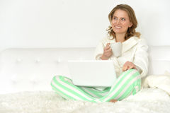 Frau mit Laptop und Tee Lizenzfreie Stockfotos