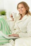 Frau mit Laptop und Tee Lizenzfreies Stockbild