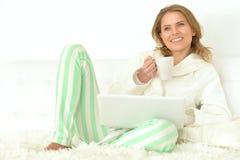 Frau mit Laptop und Tee Lizenzfreies Stockfoto
