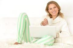 Frau mit Laptop und Tee Lizenzfreie Stockbilder