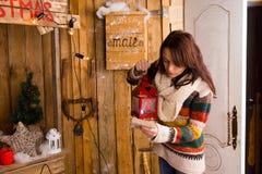 Frau mit Laternen-Lesebuchstaben am Blockhaus Lizenzfreies Stockbild