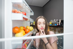 Frau mit Lebensmittel nahe Kühlschrank stockfoto