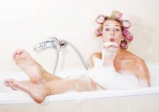 Frau mit Lockenwicklern in der Badewanne Lizenzfreies Stockfoto