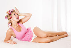 Frau mit Lockenwicklern im Bett Lizenzfreies Stockfoto