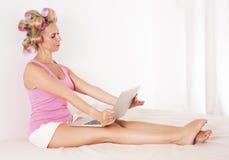 Frau mit Lockenwicklern im Bett mit Laptop Stockbild