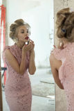 Frau mit Lockenwicklern im Spiegel korrigiert Make-up Stockfotografie