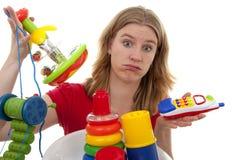 Frau mit Lots Spielwaren Stockfotos