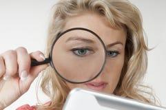 Frau mit Lupe und digitaler Tablette Stockfoto