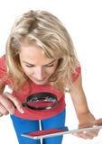 Frau mit Lupen- und Tablettencomputer Stockfotos