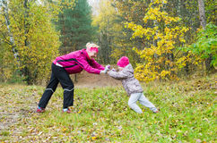 Frau mit Mädchenspiel im Herbstpark Stockfoto