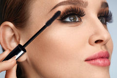 Frau mit Make-up, lange Wimpern, die Wimperntusche anwenden Handeln des Makes-up lizenzfreies stockfoto
