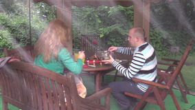Frau mit Mann sitzen nahe Tabelle mit brennenden Kerzen und essen Lebensmittel stock footage