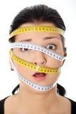 Frau mit messendem Band um ihren Kopf Lizenzfreies Stockfoto