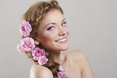Frau mit mit Flechten und Rosen im Haar Lizenzfreie Stockfotografie