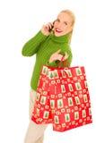 Frau mit Mobile und Beutel mit Weihnachtsgeschenken Stockfoto