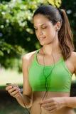 Frau mit MP3-Player hörend Musik Lizenzfreie Stockfotografie