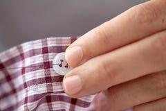 Frau mit Nadel nähend auf Knopf zum Hemd Stockfotos