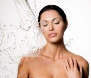 Frau mit nassem Körper und spritzt vom Wasser Stockfotografie