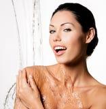 Frau mit nassem Körper und spritzt vom Wasser Stockfoto