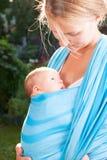 Frau mit neugeborenem Baby im Riemen Stockfoto