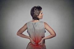 Frau mit niedrigeren Rückenschmerzen der Rückenschmerzen gefärbt im Rot Stockfotos