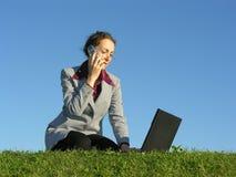 Frau mit noteboock und Telefon Lizenzfreie Stockfotos