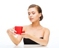Frau mit Ohrringen, Ehering und Geschenkbox Stockfotografie