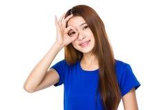 Frau mit okayzeichen auf Auge lizenzfreie stockbilder