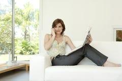 Frau mit Papier am Telefon Stockfotografie