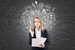 Frau mit Papieren, Internet-Suche auf Tafel Lizenzfreie Stockfotos