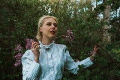 Frau mit Parfüm im Garten nahe Blumen Stockfotos