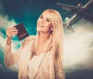 Frau mit Pass gegen blauen Himmel mit Fläche Stockbild